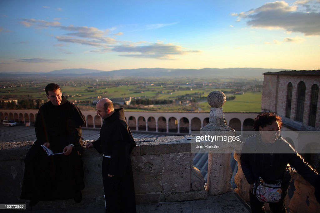 Franciscan friars relax outside the Basilica of St. Francis of Assisi which holds the tomb of Saint Francis of Assisi on March 15, 2013 in Assisi, Italy. Cardinal Jorge Mario Bergoglio took the name Pope Francis after Saint Francis of Assisi who had renounced a life of privilege, by giving away all his possessions, wearing coarse woolen clothes and living in a humble hut after he took a vow of poverty.