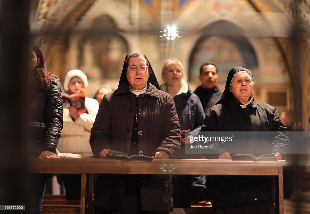 Franciscan nuns pray during a mass at the Basilica of St. Francis of Assisi which holds the tomb of Saint Francis of Assisi on March 15, 2013 in Assisi, Italy. Cardinal Jorge Mario Bergoglio took the name Pope Francis after Saint Francis of Assisi who had renounced a life of privilege, by giving away all his possessions, wearing coarse woolen clothes and living in a humble hut after he took a vow of poverty.