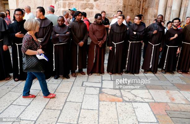 Franciscan priests prepare to enter to the Church of the Holy Sepulchre in the Old City of Jerusalem during the Good Friday procession on October 20...