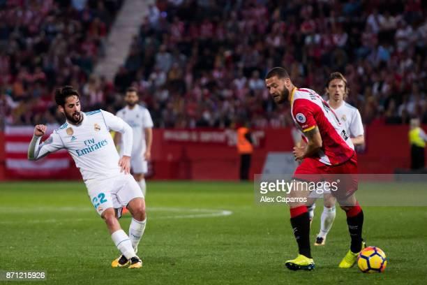 Francisco Alarcon 'Isco' of Real Madrid CF plays the ball past David Timor of Girona FC during the La Liga match between Girona and Real Madrid at...