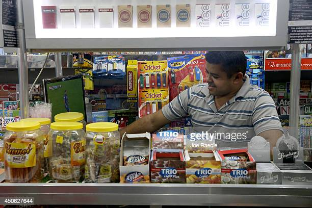Francisco Assis watches the England vs Italy 2014 FIFA World Cup match as he works at a newsstand on June 14 2014 in Rio de Janeiro Brazil Italy won...