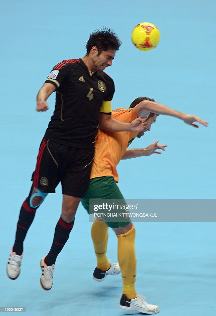 Francisco Cati of Mexico (L) battles for the ball with Fernando of Australia (R) during their first round football match of the FIFA Futsal World Cup 2012 in Bangkok on November 5, 2012. AFP PHOTO/PORNCHAI KITTIWONGSAKUL