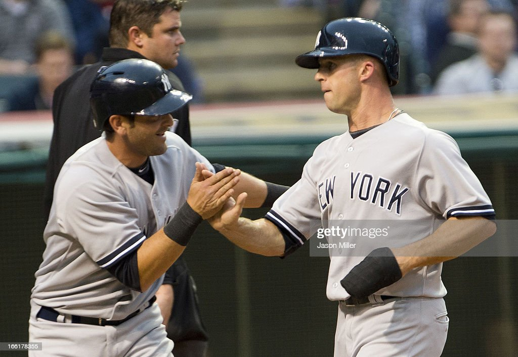 Francisco Cervelli #29 and Brett Gardner #11 of the New York Yankees celebrate after scoring on a double hit by Robinson Cano during the second inning against the Cleveland Indians at Progressive Field on April 9, 2013 in Cleveland, Ohio.