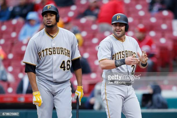Francisco Cervelli and Ivan Nova of the Pittsburgh Pirates react after Cervelli scored a run in the second inning of a game against the Cincinnati...