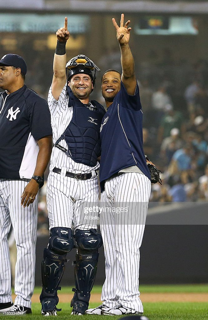 Francisco Cervelli #40 and Robinson Cano #24 of the New York Yankees celebrate the 14-2 win over the Boston Red Sox on October 3, 2012 at Yankee Stadium in the Bronx borough of New York City. With the win, the New York Yankees clinch the A.L. East Division title.