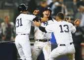 Francisco Cervelli of the New York Yankees celebrates with Ichiro Suzuki and Alex Rodriguez after he scored the winning run off of a walkoff single...