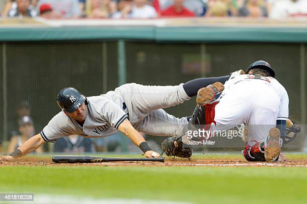 Francisco Cervelli of the New York Yankees is tagged out at home plate by catcher Yan Gomes of the Cleveland Indians to end the second inning at...