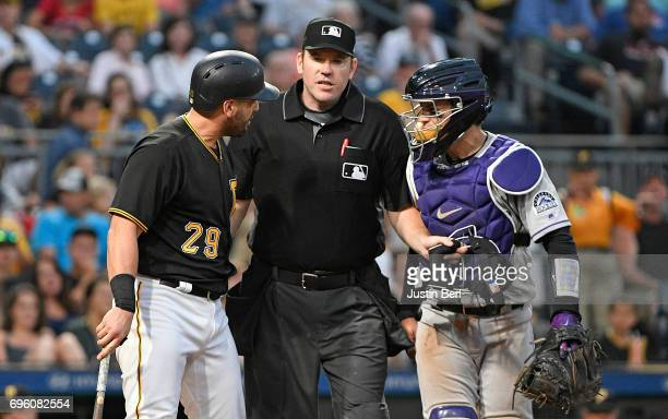 Francisco Cervelli of the Pittsburgh Pirates has words with Tony Wolters of the Colorado Rockies after being hit by a pitch in the fifth inning...