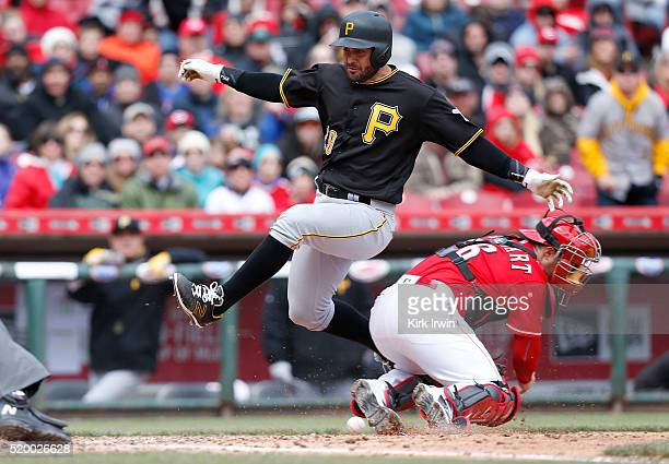 Francisco Cervelli of the Pittsburgh Pirates jumps past Tucker Barnhart of the Cincinnati Reds to score during the sixth inning at Great American...