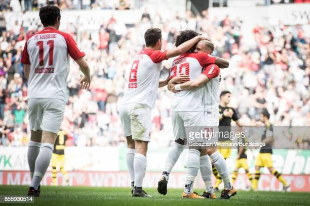 Francisco da Silva Caiuby of Augsburg celebrates scoring his teams first goal with teammates Rani Khedira and Philipp Max during the Bundesliga match...
