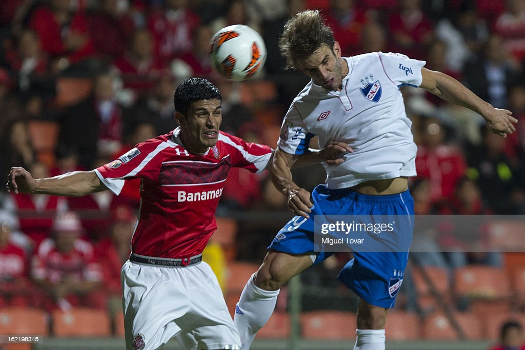Francisco Gamboa of Toluca (L) fights for the ball with <a gi-track='captionPersonalityLinkClicked' href=/galleries/search?phrase=Ivan+Alonso&family=editorial&specificpeople=2474444 ng-click='$event.stopPropagation()'>Ivan Alonso</a> of Nacional de Uruguay (R) during a match for the Bridgestone Libertadores Cup at Nemesio Diez on February 19, 2013 in Toluca, Mexico.