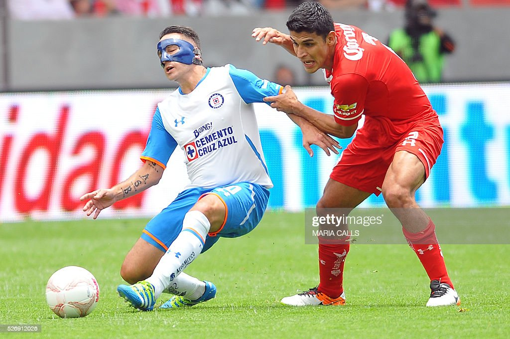 Francisco Gamboa (R) of Toluca vies for the ball with Christian Gimenez (L) of Cruz Azul during their Mexican Clausura 2016 football tournament match at Nemesio Diez stadium on May 1, 2016, in Toluca, Mexico. / AFP / MARIA