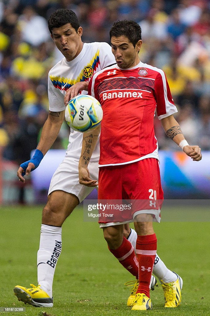 <a gi-track='captionPersonalityLinkClicked' href=/galleries/search?phrase=Francisco+Javier+Rodriguez&family=editorial&specificpeople=469708 ng-click='$event.stopPropagation()'>Francisco Javier Rodriguez</a> of America fights for the ball with Flavio Santos of Toluca during a Clausura 2013 Liga MX match between America and Toluca at Azteca Stadium on February 16, 2013 in Mexico City, Mexico.