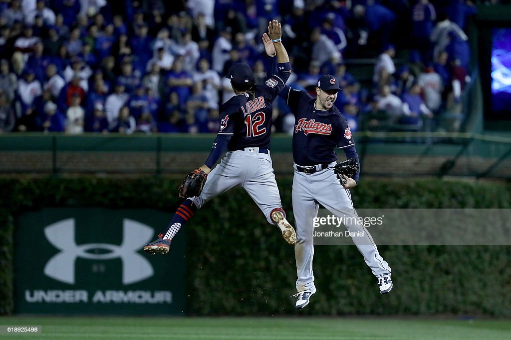 Francisco Lindor #12 and Brandon Guyer #6 of the Cleveland Indians celebrate after defeating the Chicago Cubs 1-0 in Game Three of the 2016 World Series at Wrigley Field on October 28, 2016 in Chicago, Illinois.