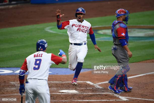 Francisco Lindor of Puerto Rico center is congratulated by Javier Baez after scoring during the first inning of World Baseball Classic Pool F Game...