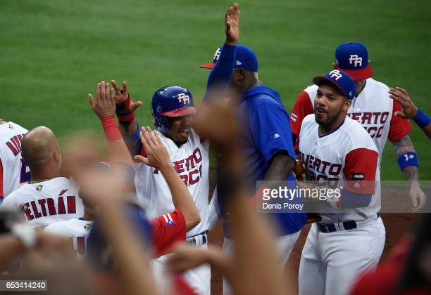 Francisco Lindor of Puerto Rico centerleft is congratulated after scoring during the first inning of World Baseball Classic Pool F Game One between...