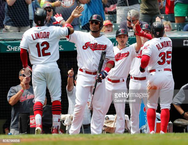 Francisco Lindor of the Cleveland Indians celebrates with Edwin Encarnacion and Abraham Almonte following Lindor's two run home run against the...