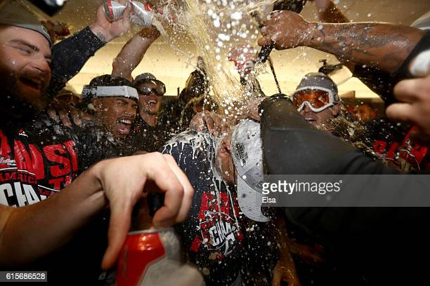 Francisco Lindor of the Cleveland Indians celebrates with his teammates by spraying manager Terry Francona in the locker room after defeating the...
