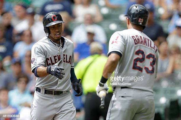 Francisco Lindor of the Cleveland Indians celebrates with Michael Brantley after hitting a solo home run in the first inning against the Milwaukee...