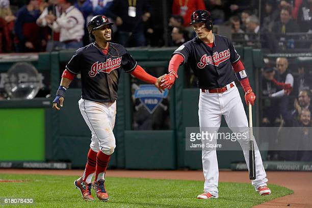 Francisco Lindor of the Cleveland Indians celebrates with teammate Brandon Guyer after scoring a run off of single hit by Jose Ramirez during the...