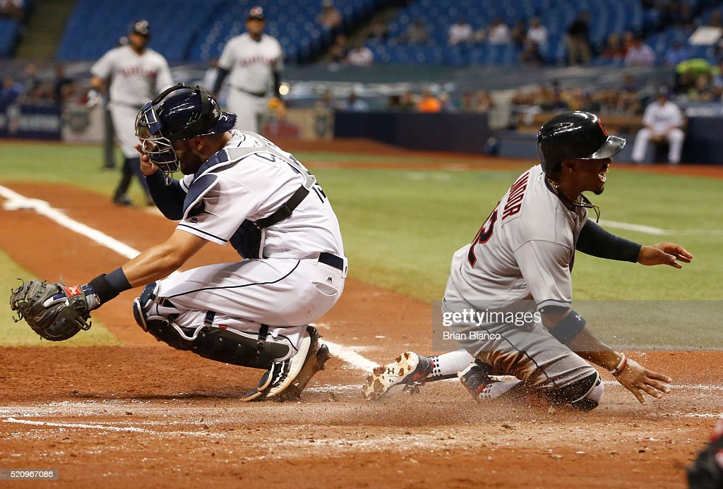 <a gi-track='captionPersonalityLinkClicked' href=/galleries/search?phrase=Francisco+Lindor&family=editorial&specificpeople=8126906 ng-click='$event.stopPropagation()'>Francisco Lindor</a> #12 of the Cleveland Indians crosses home plate ahead of catcher Curt Casali #19 of the Tampa Bay Rays to score off of a sacrifice fly by <a gi-track='captionPersonalityLinkClicked' href=/galleries/search?phrase=Carlos+Santana+-+Giocatore+di+baseball&family=editorial&specificpeople=11497843 ng-click='$event.stopPropagation()'>Carlos Santana</a> during the fourth inning of a game on April 13, 2016 at Tropicana Field in St. Petersburg, Florida.