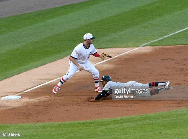 Francisco Lindor of the Cleveland Indians dives into third base as Matt Davidson of the Chicago White Sox waits for the throw during the third inning...