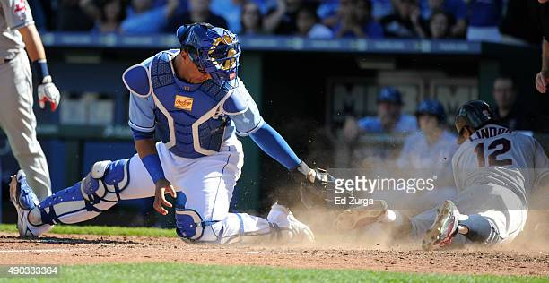 Francisco Lindor of the Cleveland Indians slides across home to score against Salvador Perez of the Kansas City Royals in the seventh inning at...