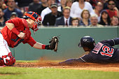 Francisco Lindor of the Cleveland Indians slides under the tag of Christian Vazquez of the Boston Red Sox in the third inning during the game at...