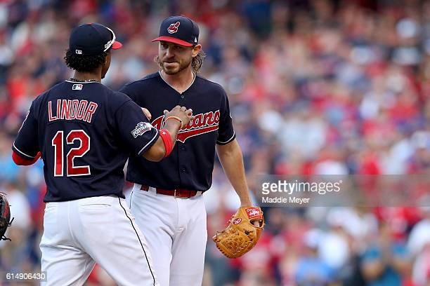 Francisco Lindor talks with Josh Tomlin of the Cleveland Indians as he walks back to the dugout after being relieved in the sixth inning against the...