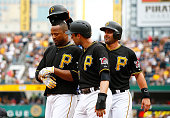 Francisco Liriano of the Pittsburgh Pirates is congratulated by teammates Neil Walker and Francisco Cervelli after hitting a three run home run in...