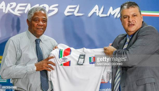 Francisco Maturana the new coach of the Once Caldas football team and the team's president Tulio Mario Castrillon hold up an Once Caldas jersey...