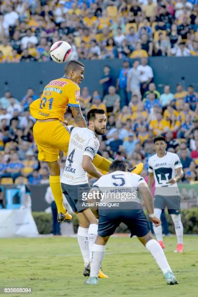 Francisco Meza of Tigres goes for a header with Luis Quintana and Alan Mendoza of Pumas during the 5th round match between Tigres and Pumas as part...