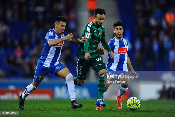 Francisco Molinero of Real Betis Balompie competes for the ball with Hernan Perez and Marcos Asensio of RCD Espanyol the La Liga match between Real...