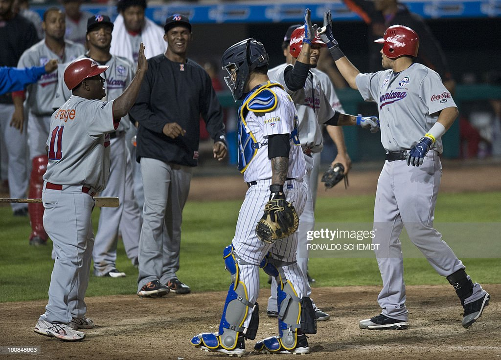 Francisco Peña (R) of Leones del Escogido of Dominican Republic, celebrates with teammates his home run against Magallanes of Venezuela, during the 2013 Caribbean baseball series, on February 6, 2013, in Hermosillo, Sonora State, in the northern of Mexico. AFP PHOTO/Ronaldo Schemidt