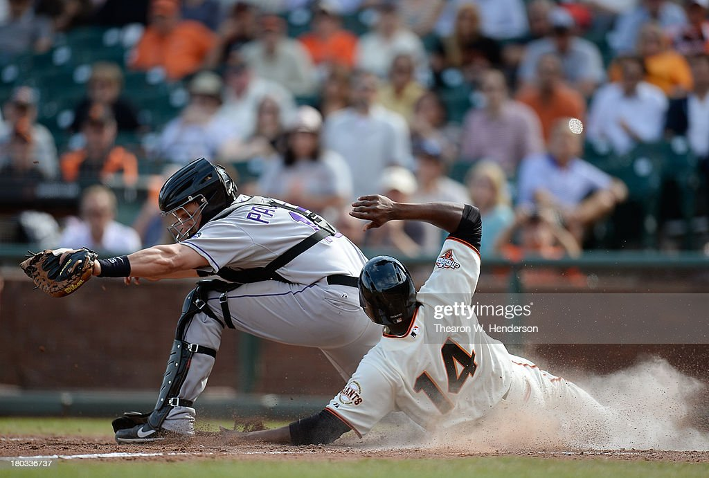 Francisco Peguero #14 of the San Francisco Giants is forced out at home plate by catcher <a gi-track='captionPersonalityLinkClicked' href=/galleries/search?phrase=Jordan+Pacheco&family=editorial&specificpeople=6889136 ng-click='$event.stopPropagation()'>Jordan Pacheco</a> #15 of the Colorado Rockies during the eighth inning at AT&T Park on September 11, 2013 in San Francisco, California. Hunter Pence #8 (not pictured) grounded into the fielders choice force out at the plate.