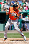 Francisco Pena of the Baltimore Orioles is hit by the pitched ball during second inning action against the Boston Red Sox during a spring training...