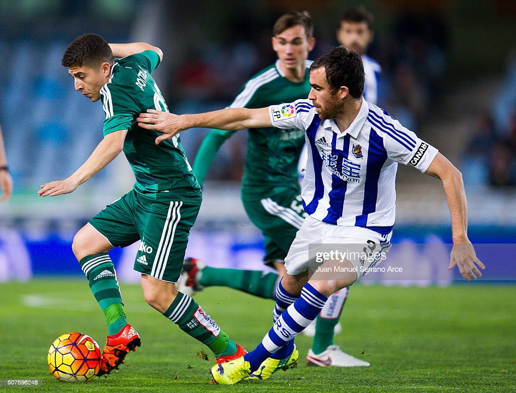 Francisco Portillo of Real Betis Balompie duels for the ball with Mikel Gonzalez of Real Sociedad during the La Liga match between Real Sociedad de...
