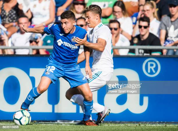 Francisco Portillo Soler of Getafe CF fights for the ball with Marcos Llorente of Real Madrid during the La Liga 201718 match between Getafe CF and...