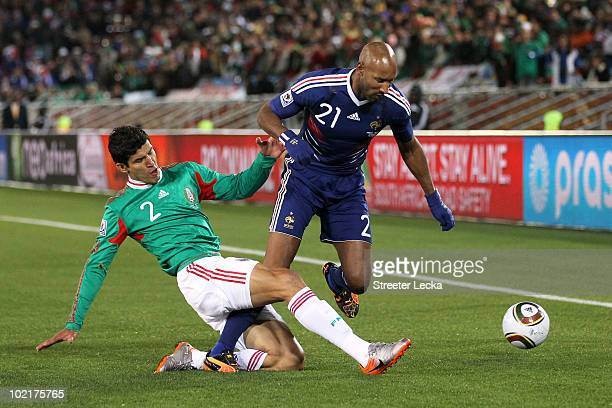 Francisco Rodriguez of Mexico tackles Nicolas Anelka of France during the 2010 FIFA World Cup South Africa Group A match between France and Mexico at...