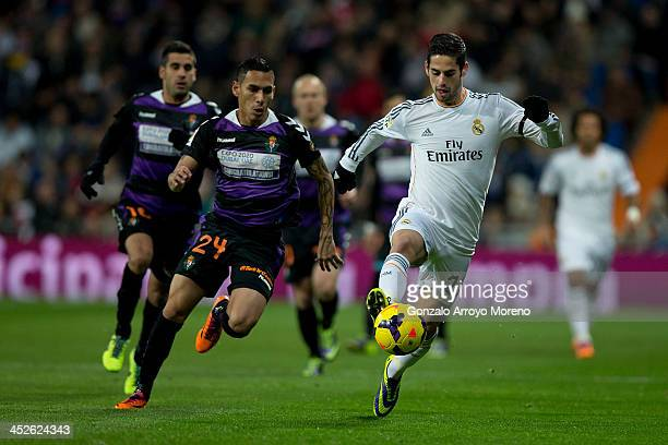 Francisco Roman Alarcon of Real Madrid competes for the ball with Gilberto Garcia of Real Valladolid CF during the La Liga match between Real Madrid...