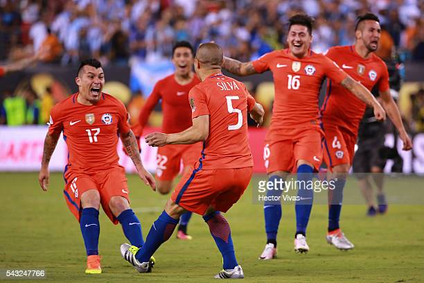 Francisco Silva of Chile celebrates with teammate after scoring the winning penalty during the championship match between Argentina and Chile at...