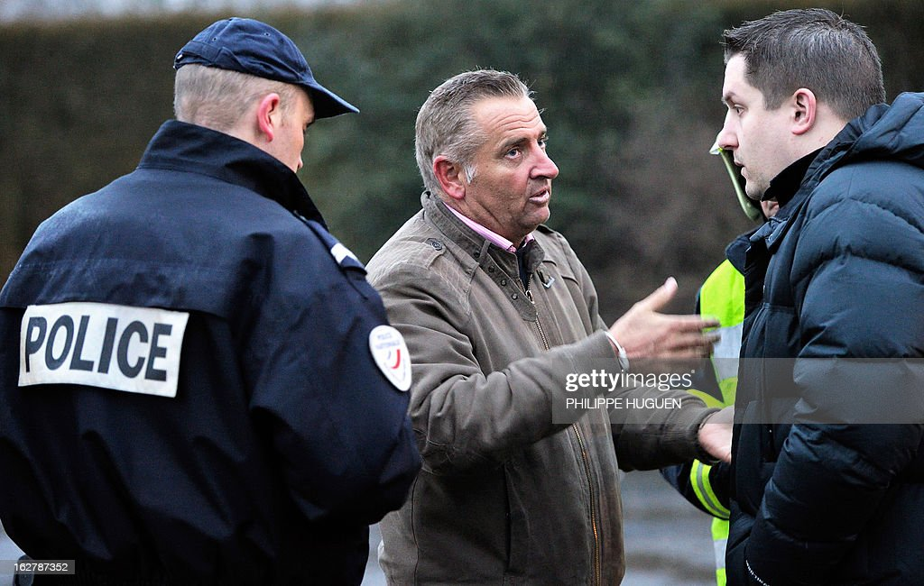 Franck Duquesne (C), owner of the nightclub 'La Fabrik' talks on February 27, 2013 with policemen after a fire swept through his nightclub in Villeneuve d'Ascq, in a suspected arson attack. A car was used to smash the door before the fire was set.
