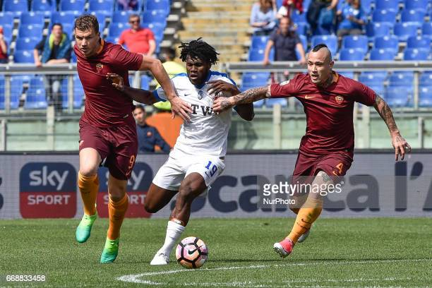 Franck Kessie of Atalanta is challenged by Edin Dzeko of AS Roma and Radja Nainggolan of AS Roma during the italian Serie A match between Roma and...