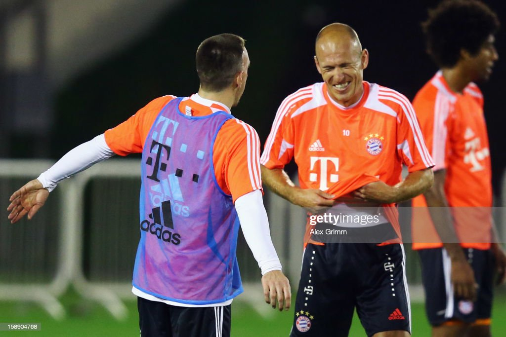 Franck Ribery ((L) and Arjen Robben laugh during a Bayern Muenchen training session at the ASPIRE Academy for Sports Excellence on January 3, 2013 in Doha, Qatar.