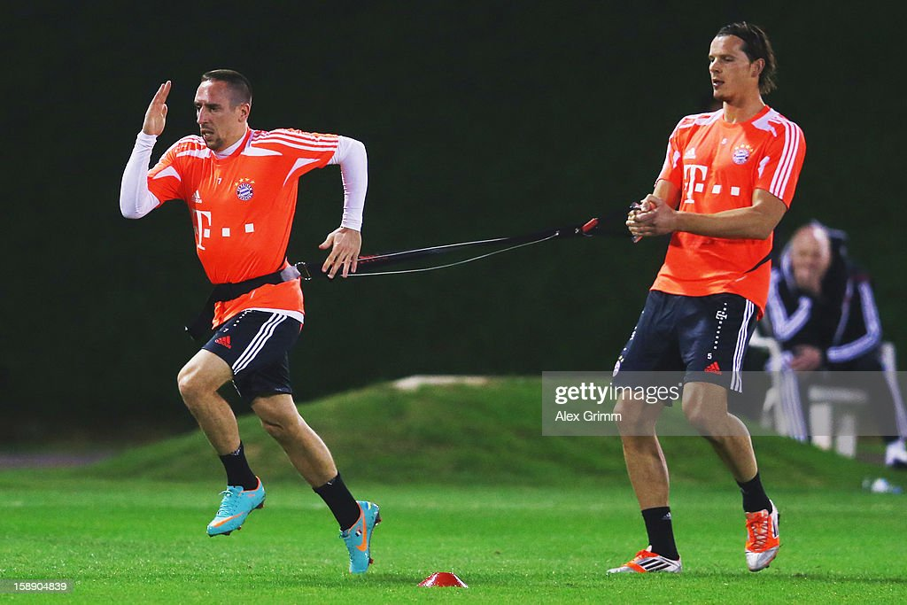 Franck Ribery (L) and Daniel van Buyten exercise during a Bayern Muenchen training session at the ASPIRE Academy for Sports Excellence on January 3, 2013 in Doha, Qatar.