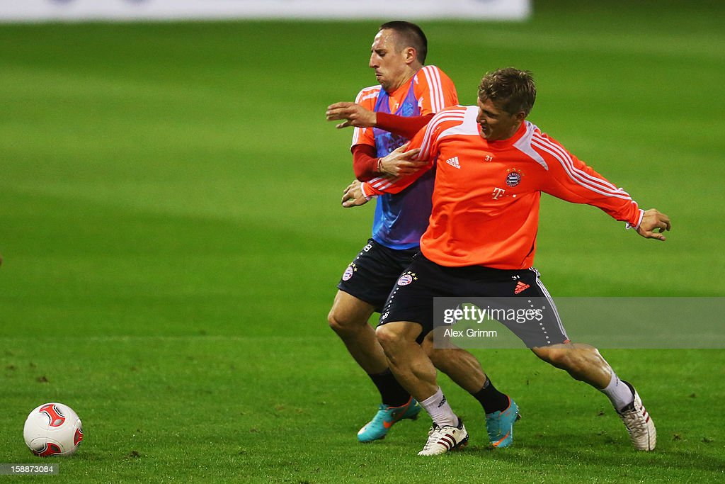 <a gi-track='captionPersonalityLinkClicked' href=/galleries/search?phrase=Franck+Ribery&family=editorial&specificpeople=490869 ng-click='$event.stopPropagation()'>Franck Ribery</a> (bqck) is challenged by <a gi-track='captionPersonalityLinkClicked' href=/galleries/search?phrase=Bastian+Schweinsteiger&family=editorial&specificpeople=203122 ng-click='$event.stopPropagation()'>Bastian Schweinsteiger</a> during a Bayern Muenchen training session at the ASPIRE Academy for Sports Excellence on January 2, 2013 in Doha, Qatar.