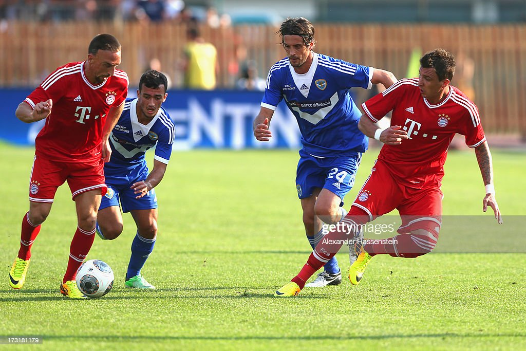 Franck Ribery (L) of Bayern Muenchen and his team mate Mario Mandzukic (R) battle for the ball with Ahmad Benali (2nd L) of Brescia and his team mate Massimo Paci during the friendly match between Brescia Calcio and FC Bayern Muenchen at Campo Sportivo on July 9, 2013 in Arco, Italy.