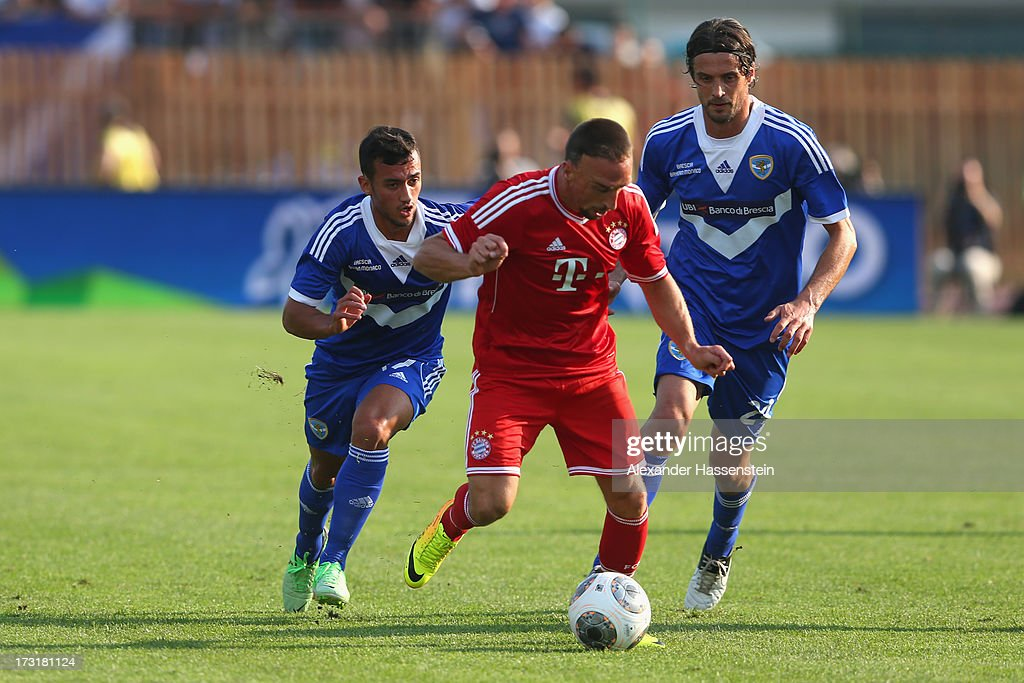 Franck Ribery of Bayern Muenchen battles for the ball with Ahmad Benali (L) of Brescia and his team mate Massimo Paci during the friendly match between Brescia Calcio and FC Bayern Muenchen at Campo Sportivo on July 9, 2013 in Arco, Italy.