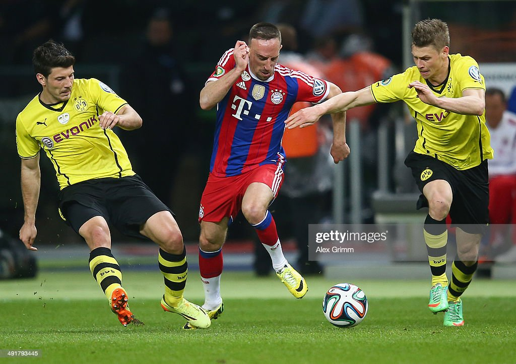 Franck Ribery (m) of Bayern Muenchen battles for the ball with Milos Jojic (l) and Lukasz Piszczek (r) of Borussia Dortmund during the DFB Cup Final match between Borussia Dortmund and FC Bayern Muenchen at Olympiastadion on May 17, 2014 in Berlin, Germany.