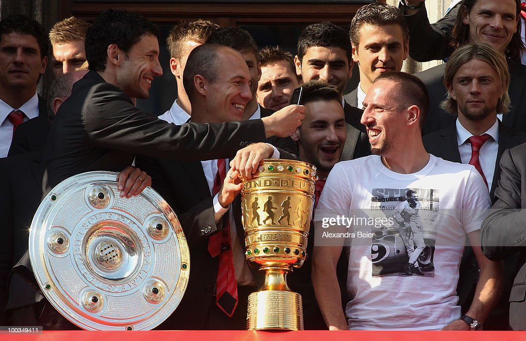 Franck Ribery (R) of Bayern Muenchen smiles to Mark van Bommel (L) and Arjen Robben after he confirmed to extend his contract until 2015 for Bayern Muenchen during a celebration of their two titles (German Championship and German Soccer Cup) at the balcony of the town hall on May 23, 2010 in Munich, Germany. Bayern Muenchen lost the Champions League Final match against Inter Milan on Saturday.